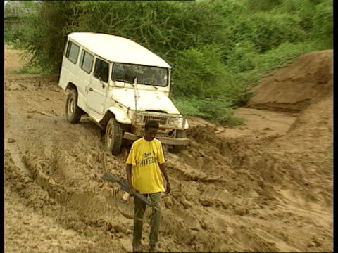 relief problem; tms people sitting & standing around in camp armed man escorting vehicle thru difficult, very muddy terrain pull out int/vehicle cms... - horn of africa stock videos & royalty-free footage