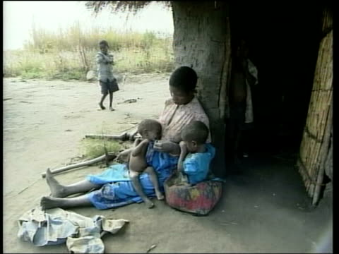 vídeos de stock e filmes b-roll de southern africa famine appeal lib africa malawi lilongwe ext ms woman sitting outside hut with two small children cms child crying tms small starving... - malávi