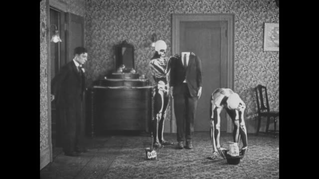 vídeos de stock e filmes b-roll de 1921 disbelieving man (buster keaton) is startled as he watches two skeletons assemble man who comes to life - mansão imponente