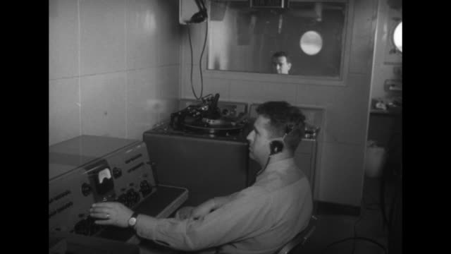 disc jockey at radio board turntable beside him as voice of america broadcasts from on board the uscgc courier / cu floating turntable with vinyl... - coast guard stock videos and b-roll footage