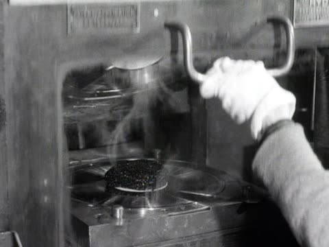 disc of wax is pressed to produce a gramophone record in a record factory. - ディスク点の映像素材/bロール