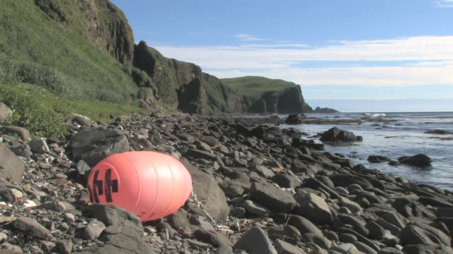 discarded buoy on pebble beach. aleutian islands, bering strait - aleutian islands stock videos and b-roll footage