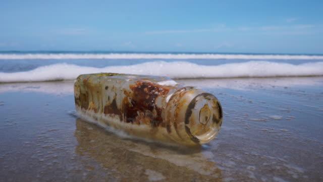 kunststoff-flasche müll verschmutzung am strand verworfen - umweltthemen stock-videos und b-roll-filmmaterial
