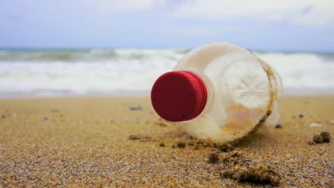 vídeos y material grabado en eventos de stock de descartan contaminación de basura de plástico de la botella en la playa - botella