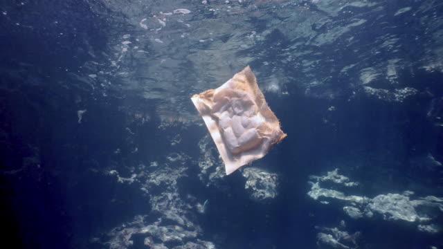 vídeos de stock, filmes e b-roll de embalagens de alimentos de plástico descartados poluindo o ponto de vista subaquático do mar - vida no mar