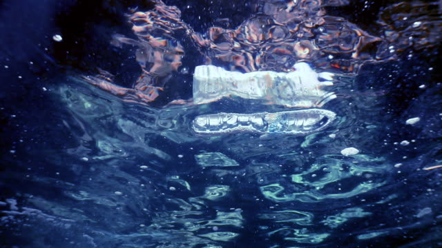 discarded plastic water bottle polluting the sea - bottiglia video stock e b–roll