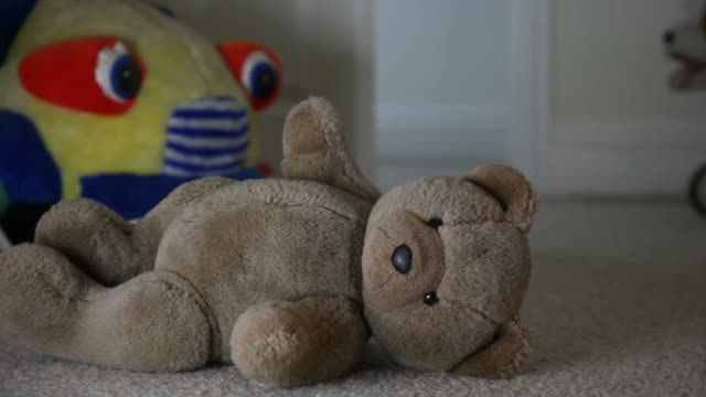Discarded Teddy bear, child's room, man walks in.