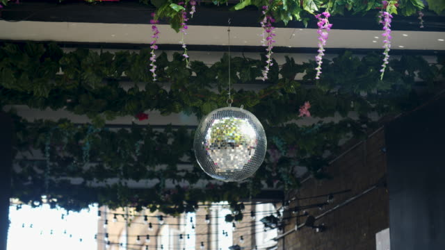a disco ball glitters in an alleyway decorated with fake foliage and flowers - street style点の映像素材/bロール