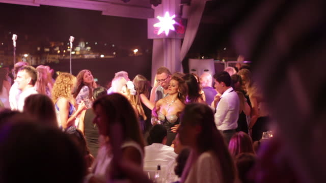 disco party ibiza with color lights and people dancing - イビサ島点の映像素材/bロール