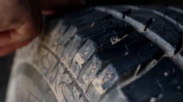vídeos de stock, filmes e b-roll de descoberto o parafuso que causou o pneu ir plana - tyre