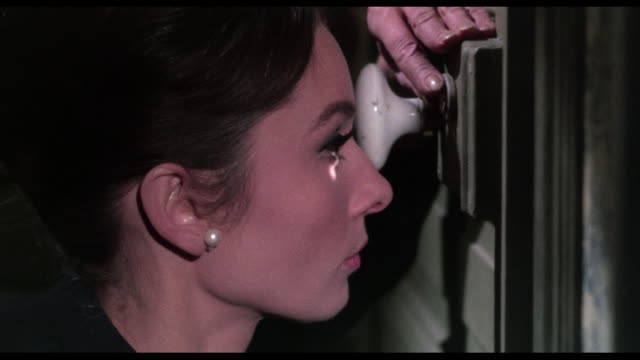 1963 discovering a man's deception, a woman (audrey hepburn) sneaks out of hotel - 嘘点の映像素材/bロール