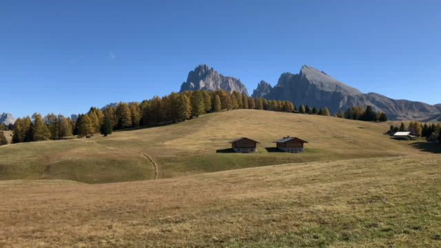 discovering the beautiful dolomites mountains with meadows and alpine houses in alpe di siusi. - alpe di siusi video stock e b–roll