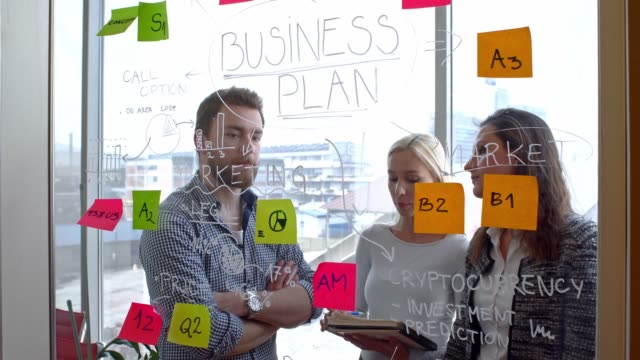 Discussing a business plan written on glass