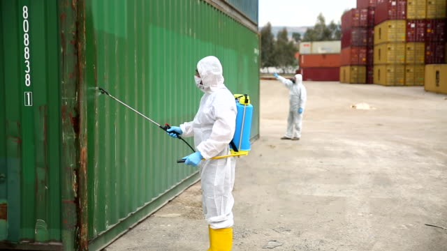 disease control service staff disinfect cargo to prevent spread covid-19 - biohazard symbol stock videos & royalty-free footage