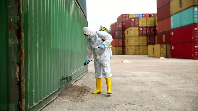il personale del servizio di controllo delle malattie disinfetta il carico per prevenire la diffusione del covid-19 - box container video stock e b–roll