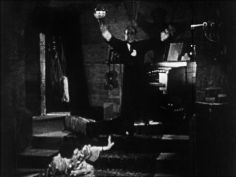 b/w 1925 disfigured man (lon chaney, sr.) approaching woman (mary philbin) on floor / feature - 1925 stock videos & royalty-free footage