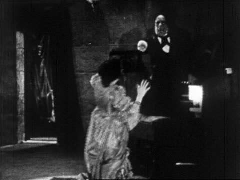 b/w 1925 disfigured man (lon chaney, sr.) pointing as woman (mary philbin) falls to knees / feature - 1925 stock videos & royalty-free footage