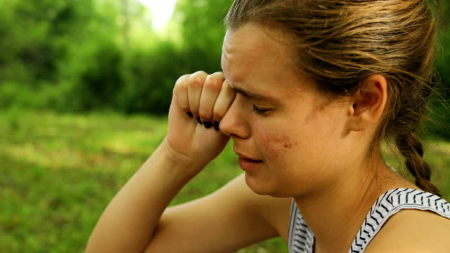 disgusted young woman rubbing her eyes in nature - rubbing stock videos & royalty-free footage