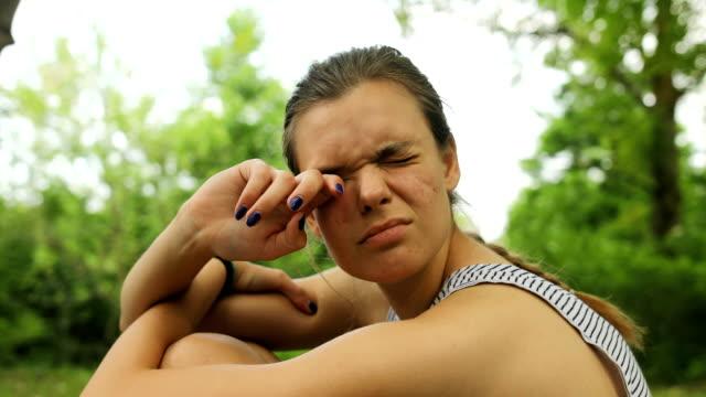 vídeos y material grabado en eventos de stock de mujer joven disgustada frotándose los ojos en la naturaleza - enfermedad contagiosa