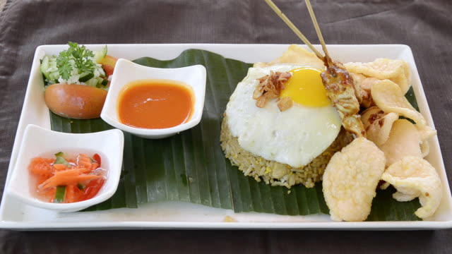 cu dish of nasi goreng with fried rice, chicken, egg, kerupuk crackers, pineapple juice and balinese food at asia / ubud, bali, indonesia - crockery stock videos & royalty-free footage