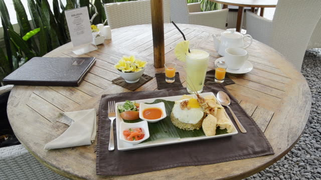 ms dish of nasi goreng with fried rice, chicken, egg, kerupuk crackers, pineapple juice and balinese food at asia / ubud, bali, indonesia - fried rice stock videos and b-roll footage