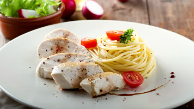 4K A dish of spaghetti with chicken and cherry tomato.