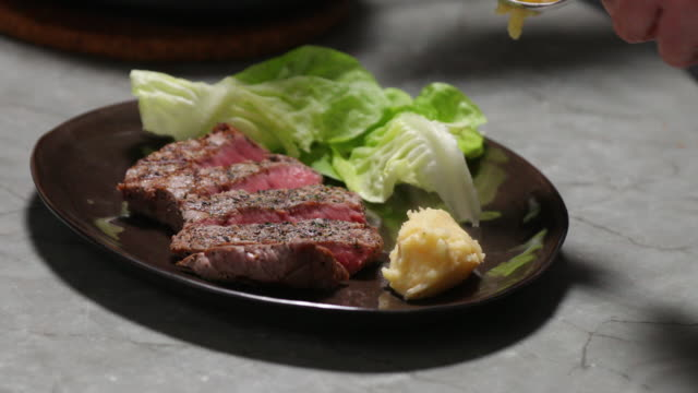 Dish with grilled steak, potato puree and lettuce.