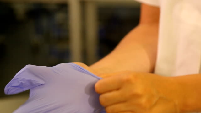 cu disinfecting hands with sanitizer and placing on blue gloves/ south africa - scrubs stock videos & royalty-free footage