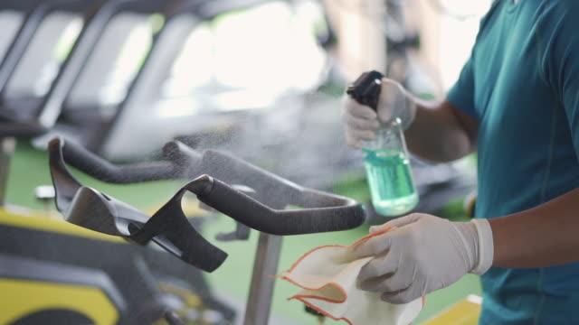 vídeos de stock, filmes e b-roll de desinfetando superfícies de vírus na academia com lenço umedecido. - equipamento para exercícios