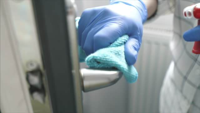 disinfecting the door handle at home. - glove video stock e b–roll