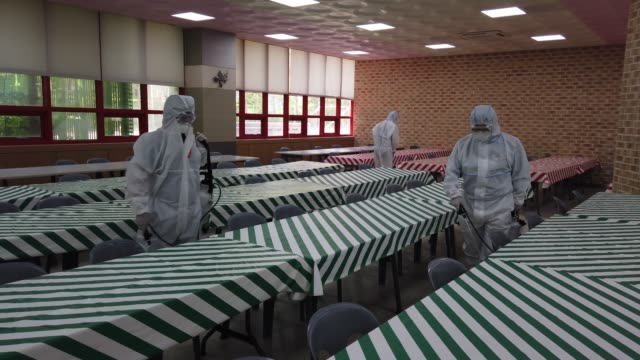 disinfection professional and government official wearing protective clothing spray antiseptic solution at classroom to prevent the spread of the... - prevention stock videos & royalty-free footage