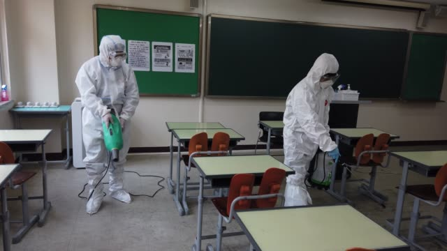 stockvideo's en b-roll-footage met disinfection professional and government official wearing protective clothing spray antiseptic solution at classroom to prevent the spread of the... - heropening