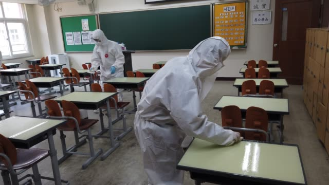stockvideo's en b-roll-footage met disinfection professional and government official wearing protective clothing spray anti-septic solution at classroom to prevent the spread of the... - heropening