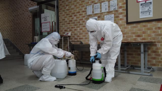 disinfection professional and government official wearing protective clothing spray antiseptic solution at classroom to prevent the spread of the... - korea bildbanksvideor och videomaterial från bakom kulisserna