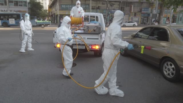 disinfection workers wearing personal protective equipment , disinfect a street to prevent the coronavirus spread on october 06 in seoul, south... - korean new year stock-videos und b-roll-filmmaterial