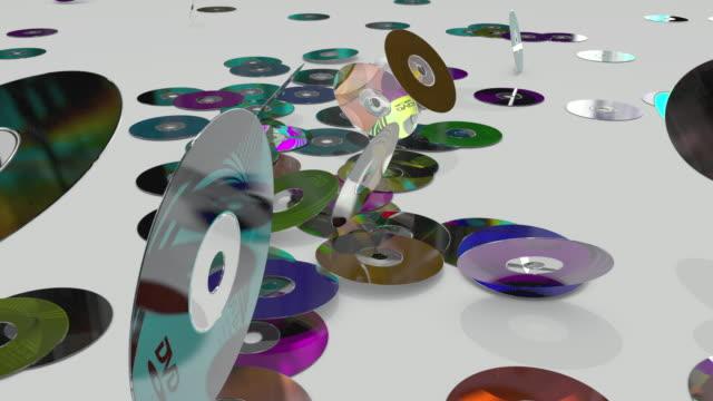 vídeos de stock, filmes e b-roll de ws slo/ mo dvd disks tossing on  flat surface - dvd cd