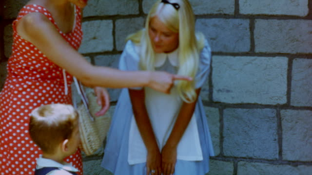 a disney character playing alice in wonderland greets a young boy the following shot is of the dumbo flying elephant ride - disney stock videos and b-roll footage