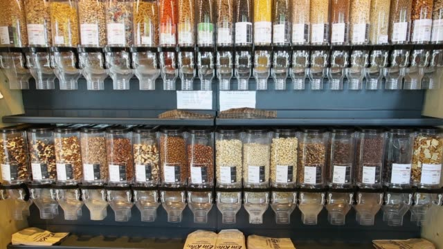 vídeos de stock, filmes e b-roll de dispensers filled with nuts hang on display at a veganz vegan grocery store on february 2 2018 in berlin germany veganz has three stores in berlin... - vegan