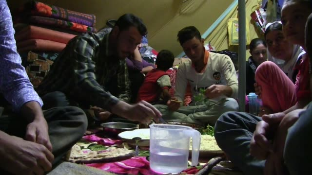displaced family from the minority yazidi sect driven from their homes in sinjar by islamic state militants eating a meal at a refugee camp in the... - sinjar stock videos & royalty-free footage