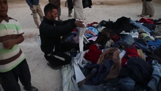 Displaced Syrians buy second hand winter clothes at the Kafr Lusin camp in northern Idlib province near the border with Turkey as they prepare for...