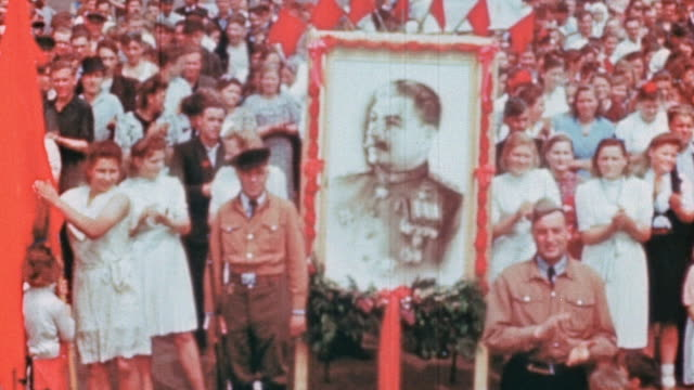 displaced workers celebrating ve day with soviet flags and portrait of stalin, applauding speaker / germany - russian flag stock videos & royalty-free footage