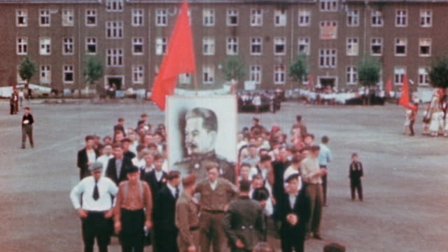 displaced workers celebrating ve day with soviet flags marching parades and portrait of stalin / germany - ve day stock-videos und b-roll-filmmaterial