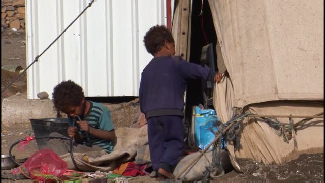 displaced yemeni mother and children sit inside their tent - yemen stock videos and b-roll footage