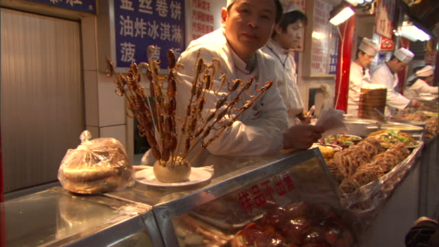 SLO MO ZI CU Display of bugs, scorpions and seahorses on sticks atop busy food counter, Beijing, China