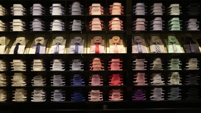 display of coloured men's shirts and ties sit on shelves inside hugo boss ag's store on regent street in london, r-l interior of the men's department... - hugo boss stock videos & royalty-free footage