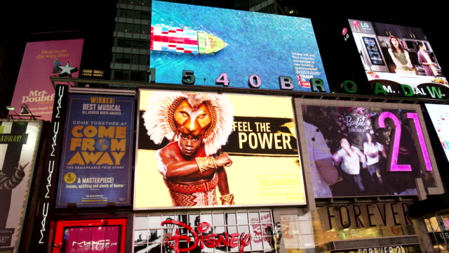 vídeos de stock e filmes b-roll de display of electronic billboard advertisements in times square at night broadway and 7th avenue. - painel publicitário eletrónico