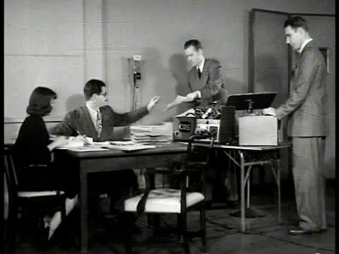 Display of Norman Corwin books records American writer Norman Corwin sitting at desk w/ female assistant two young adult males in suits standing at...