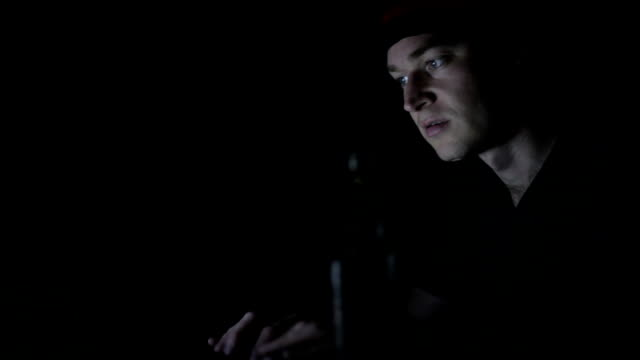 Displeased man working on computer in the dark