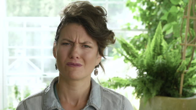 displeased mid adult woman frowning. - suspicion stock videos & royalty-free footage