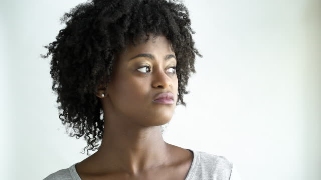 displeased young woman with afro, studio shot. - displeased stock videos and b-roll footage